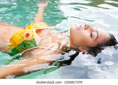 Portrait of beautiful young healthy woman in bikini, floating in water with reflections, wellness spa outdoors. Exotic female relaxing in vacation retreat, leisure recreation lifestyle, beauty living.