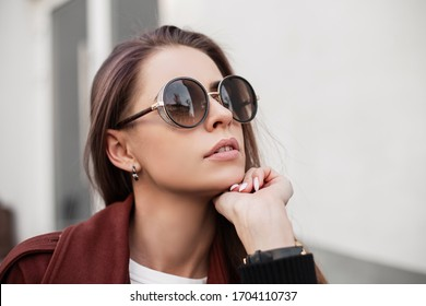 Portrait beautiful young hipster woman in trendy dark sunglasses in stylish brown cloak outdoors in the city. Attractive girl fashion model with clean skin with sexy lips on the street. Close-up