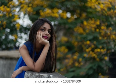 Portrait of a beautiful and young Indian Bengali brunette girl in blue western dress leaning on the side of rooftop in the afternoon with a tree full of yellow flowers in background. Indian lifestyle