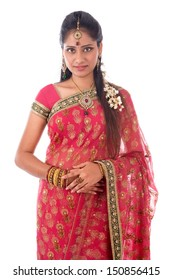 Portrait of beautiful young Indian woman in traditional sari dress standing isolated on white background.