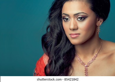 Portrait of a beautiful young indian/asian model with long hair, isolated on blue