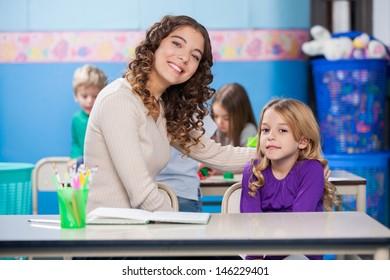 Portrait of beautiful young kindergarten teacher with arm around little girl in classroom
