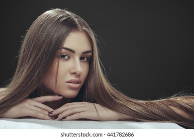 Portrait of beautiful young lady with long silky straight brown hair posing in studio over dark grey background. Hair care.