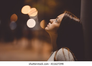 Portrait of beautiful young lady looking up, city street in the night, evening lights bokeh outdoors background