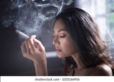 Portrait of beautiful young lady smoking cigarette with emotional facial expression.
