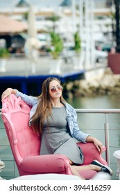 Portrait of beautiful young lady in sunglasses sitting in elegant armchair. Pretty girl in grey dress smiling on blurred embankment cafe outdoor background.