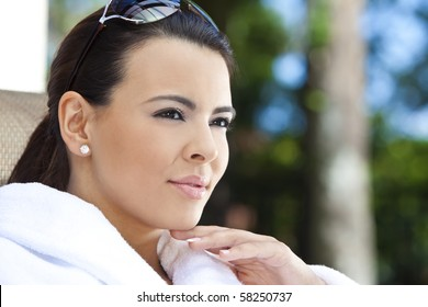 Portrait of a beautiful young Latina Hispanic woman smiling in a white bathrobe outside at a health spa