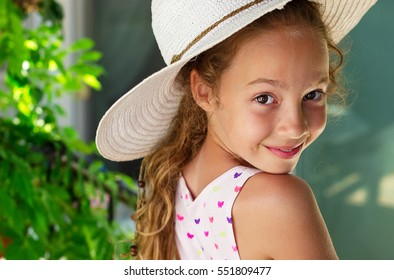 Portrait of a beautiful young little girl on the background of summer park. Cute kid Girl enjoying summer holidays vacation outdoor.