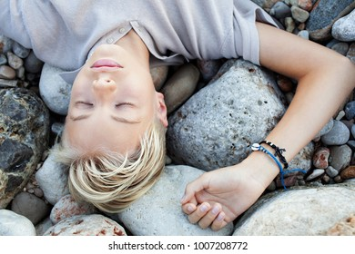 Portrait of beautiful young man laying on beach rocks with texture relaxing with eyes closed on summer holiday, outdoors nature discovery. Travel visit vacation, teenager sleeping, healthy lifestyle.