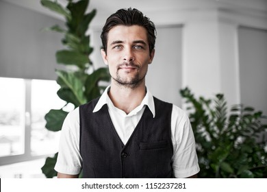 Portrait of a beautiful young man in the office. He looks well-groomed. The guy smiles and looks at the camera. He has good clothes. in the background house plants.
