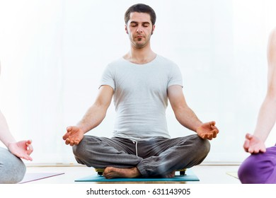 Portrait of beautiful young man practicing yoga at home. Sukhasana pose.
