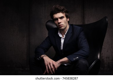 Portrait of a beautiful young man sitting in a chair. Stylish in appearance. Casual suit of dark concrete wall background