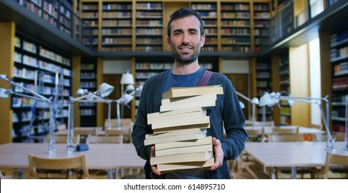 Portrait of a beautiful young man smiling happy in a library holding books after doing a search and after studying. Concept: educational, portrait, library, and studious.
