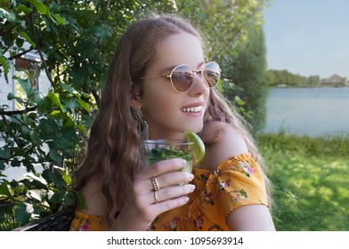 portrait of beautiful young millennial teen girl in summer. drinking mojito cocktail in park at lake, smiling and wearing sunglasses