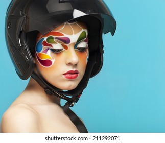 Portrait of a beautiful young model with bright creative make up with helmet