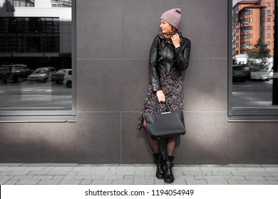 Portrait of a beautiful young model in brown knitted hat standing do to work, on background mirrow wall on  sunny autumn day in  big city. Autumn warm photo.Woman smiling and look away