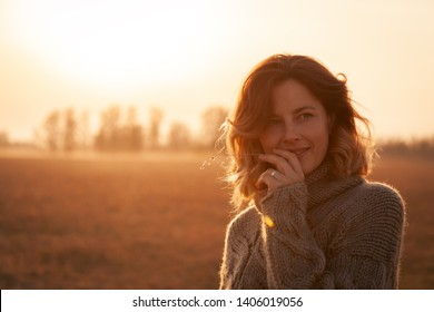 Portrait of a beautiful young model in knitted hat  and warm clothes enjoy day, on background field in  sunny autumn day. The concept of the unity of women and nature, peaceful mood, eco-friendly life