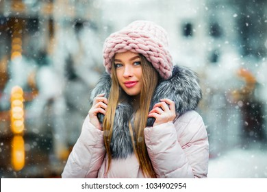 Portrait of a beautiful young model in pink knitted hat standing near carousel on a christmas background with bokeh lights. Magic warm new year photo.Cozy background. Happy woman.