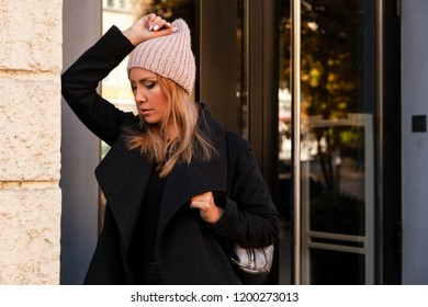 Portrait of a beautiful young model in pink knitted hat standing do to work, on background mirrow wall on  sunny autumn day in  big city. Autumn warm photo.Woman smiling and look away, joyful cheerful