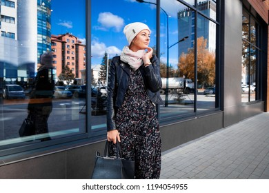 Portrait of a beautiful young model in white knitted hat standing do to work, on background mirrow wall on  sunny autumn day in  big city. Autumn warm photo.Woman smiling and look away