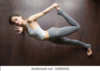 Portrait of beautiful young model working out in home interior or sport club, doing yoga exercise on wooden floor, standing in Partridge yoga pose, arm balance Kapinjalasana. Top view. Full length