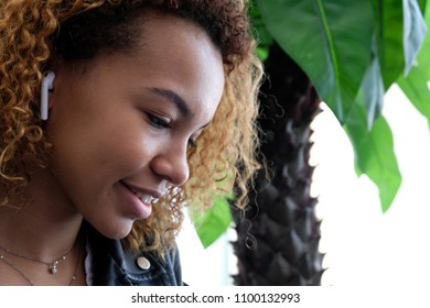 Portrait of a beautiful young modern black woman, in a leather jacket with airpods in her ear, listens to music. African American girl smiling, looking down.