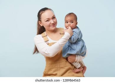 Portrait of a beautiful young mother in beige overalls holding adorable little baby girl in jeans dress in her arms against pale blue background. Baby sucking on mother's finger.