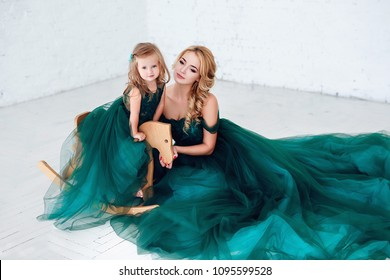 Portrait of a beautiful young mother with a cute blonde daughter sitting in white interior dressed in elegant green dresses.