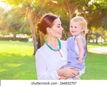 Portrait of beautiful young mother with cute little daughter on hands spending summer day in fresh green park, having fun outdoors, love and happiness concept