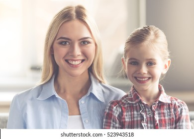 Portrait of beautiful young mother and her cute little daughter looking at camera and smiling