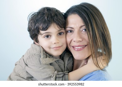 Portrait of beautiful young mother with his son sitting cheek to cheek, smiling and happy against blue background.