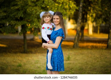 Portrait of beautiful young mother hugging first-grader daughter in festive school uniform on background autumn park.