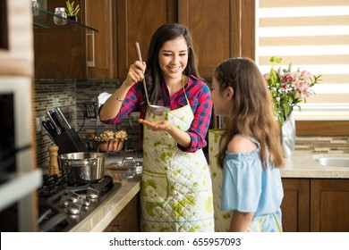 Portrait of a beautiful young mother offering some hot sauce to her daughter to taste