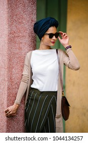Portrait of a beautiful, young Muslim Arab woman (Asian) leaning against a pastel colored wall in the day. She is tall, slim and fashionably dressed in a turban, an elegant outfit and sunglasses.