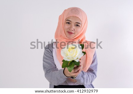 portrait of beautiful young muslim girl holding a white rose flower on white background.