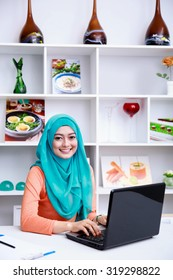 portrait of beautiful young muslim woman working on her laptop at office with decorated shelf at background