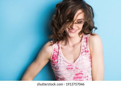 Porträt einer schönen jungen natürlichen Frau mit einem gesunden Lächeln und geschlossenen Augen nahe einer blauen Wand. Studioaufnahme.