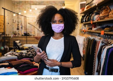 Portrait of beautiful young owner of a clothing store holding a tablet at entrance of the business while waiting customers wearing a protective face mask against Coronavirus infections, Covid-19