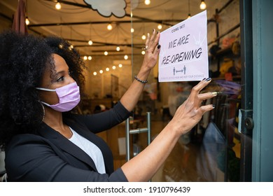 Portrait of a beautiful young owner of a clothing store while hanging a sign in the window for the reopening of the business wearing the protective face mask against Coronavirus infections, Covid-19 - Shutterstock ID 1910796439
