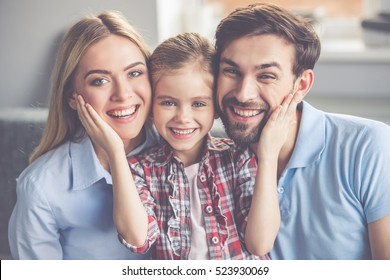 Portrait of beautiful young parents and their cute little daughter hugging, looking at camera and smiling