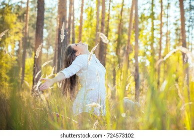 portrait of a beautiful young pregnant girl in a trendy dress against the background of an autumn forest