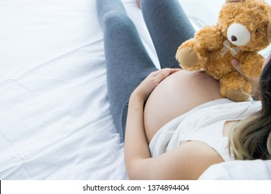 Portrait of Beautiful young pregnant woman in her bedroom.Pregnancy health care preparing for baby concept.Motherhood among teenage mother.