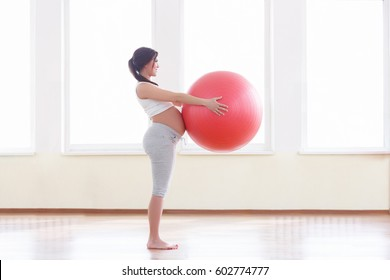 Portrait of a beautiful young pregnant woman exercises with red fitball in the gym. Working out and fitness, pregnancy concept.
