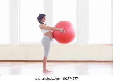 体育館で赤いフィットボールを使って運動する美しい妊婦のポートレート。働き、健康、妊娠のコンセプト。