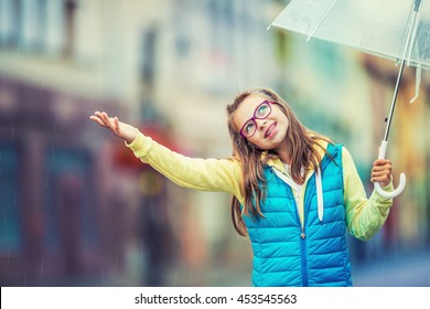 Portrait of beautiful young pre-teen girl with umbrella under rain.