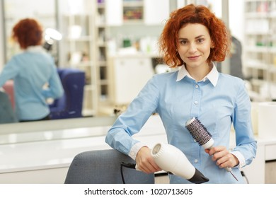 Portrait of a beautiful young red haired female hairdresser posing at her workplace at the beauty salon holding a brush and blow dryer smiling to the camer copyspace staff employee career job.