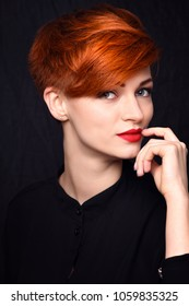 Portrait of a beautiful young red-haired woman with short hair on a dark background
