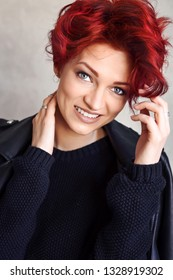 Portrait of a beautiful young red-haired woman with short hair looking at camera.