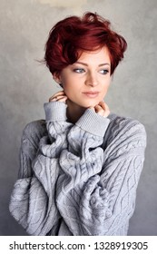 Portrait of a beautiful young red-haired woman with short hair wearing warm woolen sweater