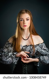 Portrait of a beautiful young redhead girl with perfect make up and shiny hair on dark gray background. Fairytale gothic story with braided lady.